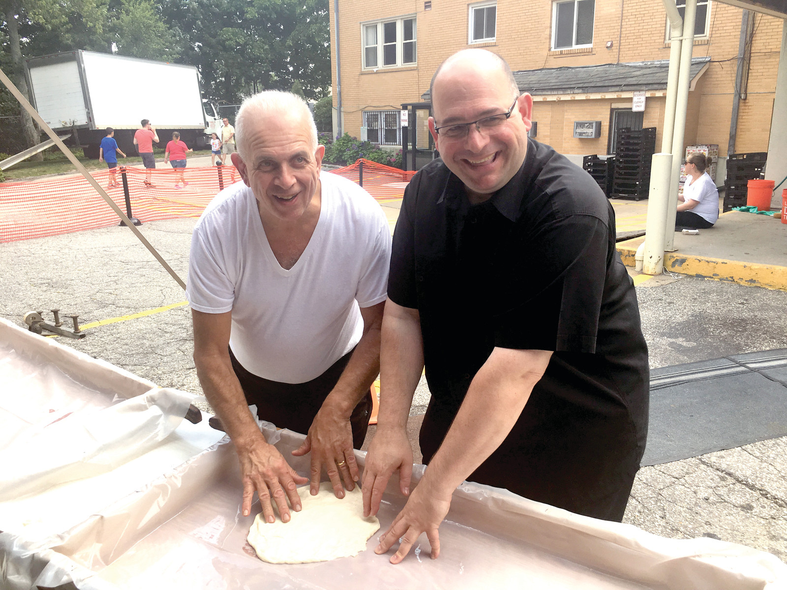 STICKY SITUATION: Don DePetrillo donates much to the Johnston community. He's pictured here with Father Carusi, the Pastor at St. Rocco's School, kneading some of the more than 1,000 pounds of dough he donated to the event. Parishioners thank DePetrillo for donating his time and money to the church and community.