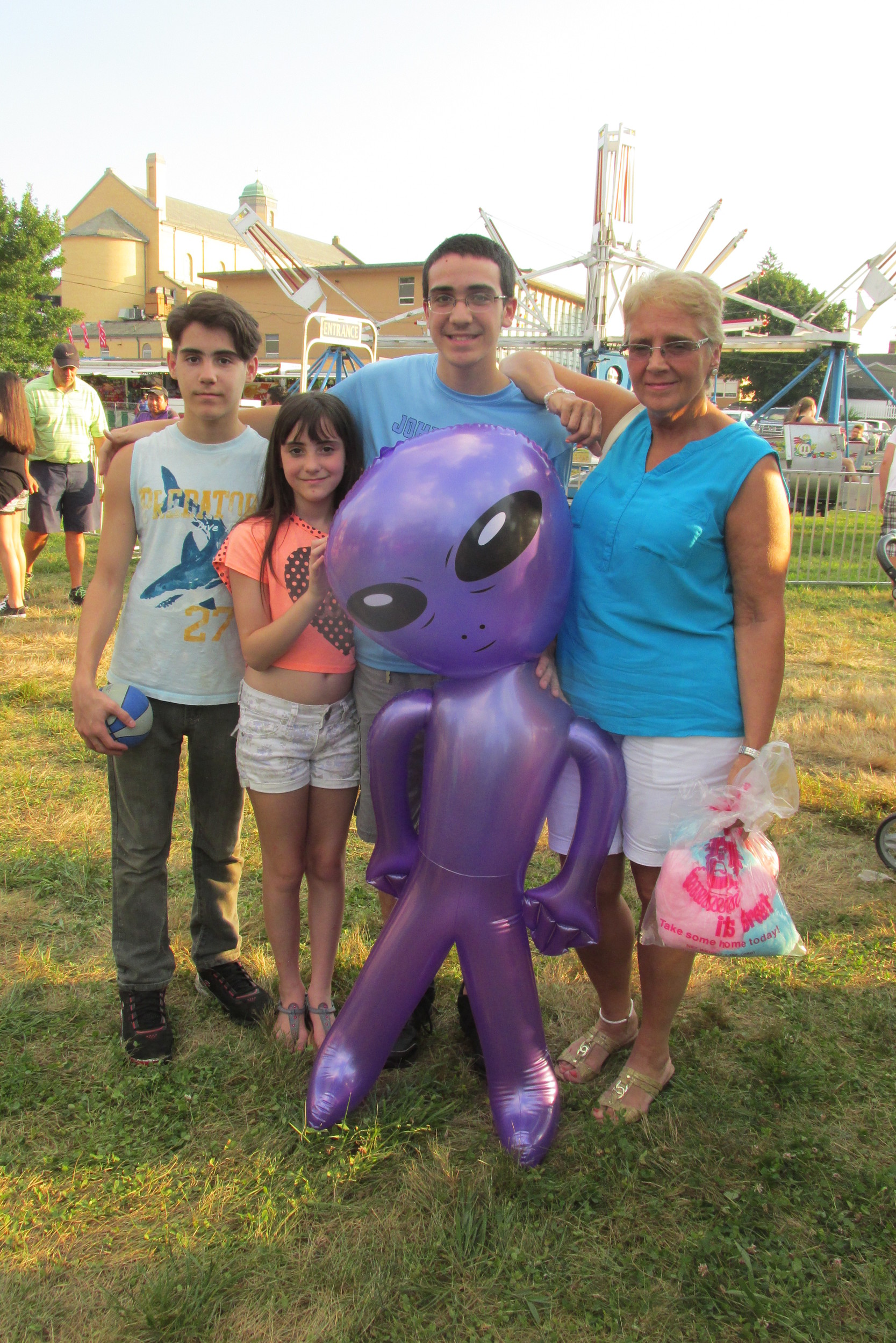 "GRAM'S GROUP: Gemma DeSiano (right) was one of the many folks who took their grandchildren to the annual Saint Rocco Feast and Festival. Her kids are: Devin Cali, Dylan McConaghy who won a ""Mister Alien"" blow-up creature at the Rockwell Amusements carnival."