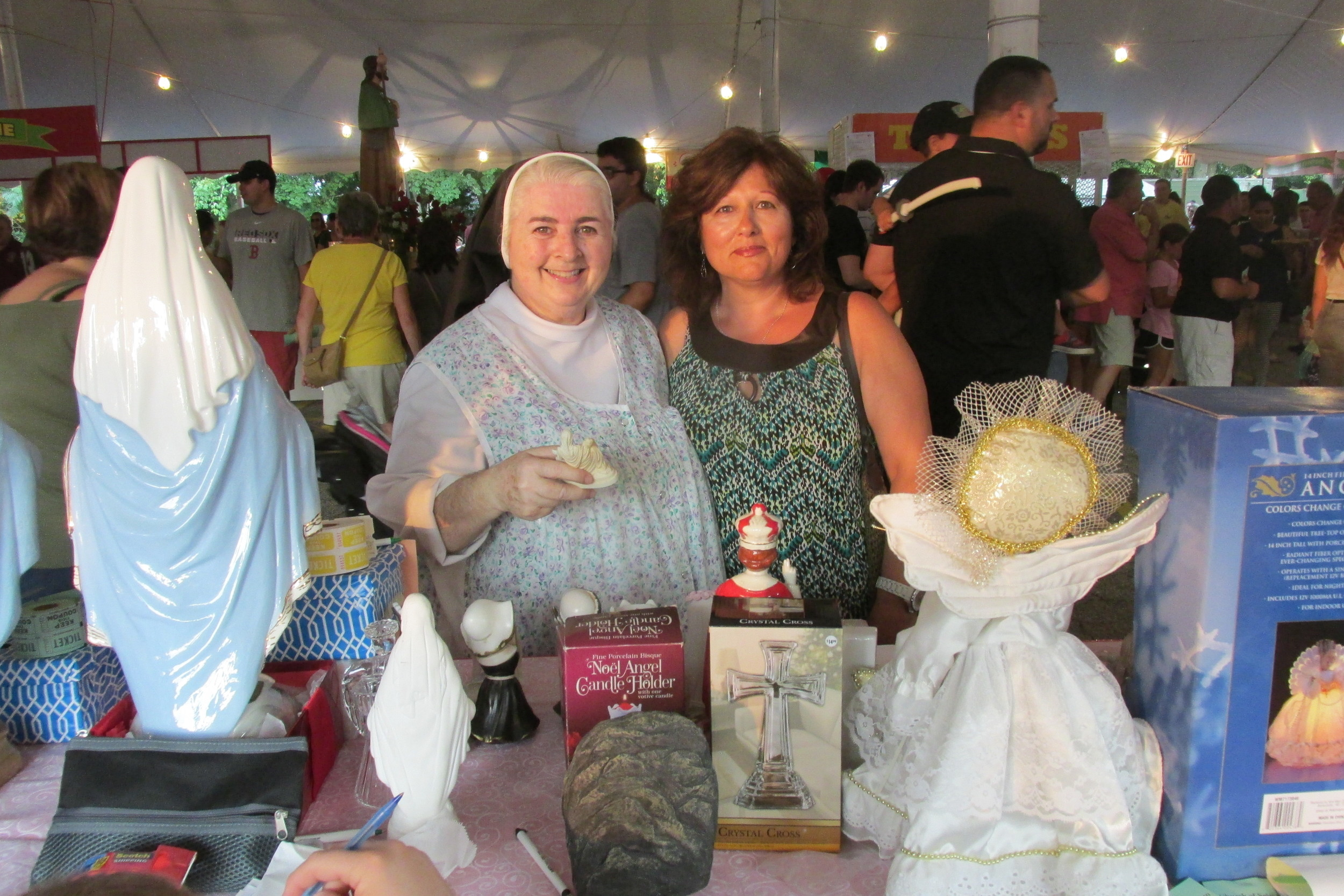 IMPORTANT ITEMS: Sister Donna joins Nancy Levesque at the Religious Stand that was quite popular with people attending the Saint Rocco Church Feast and Festival.