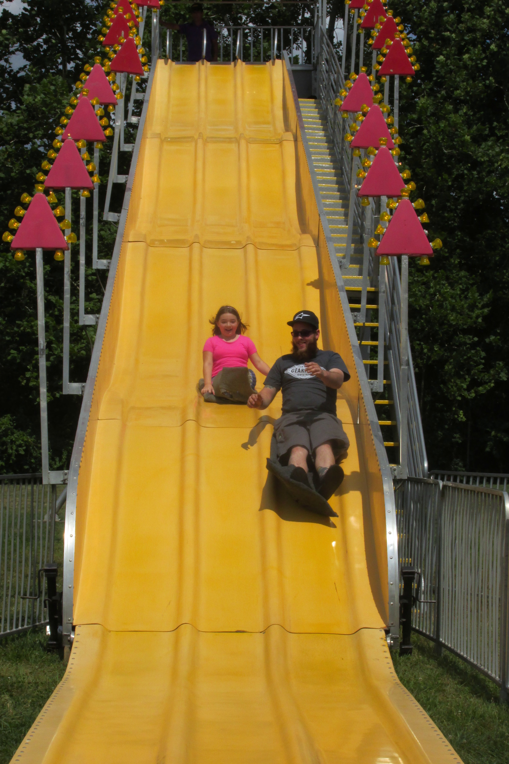 SUPER SLIDE: Randy Leary and his daughter Sylvia, 9, enjoy the thrills while zooming down the Fun Slide during Sunday's Rockwell Amusements Carnival at Saint Rocco Church in Johnston.