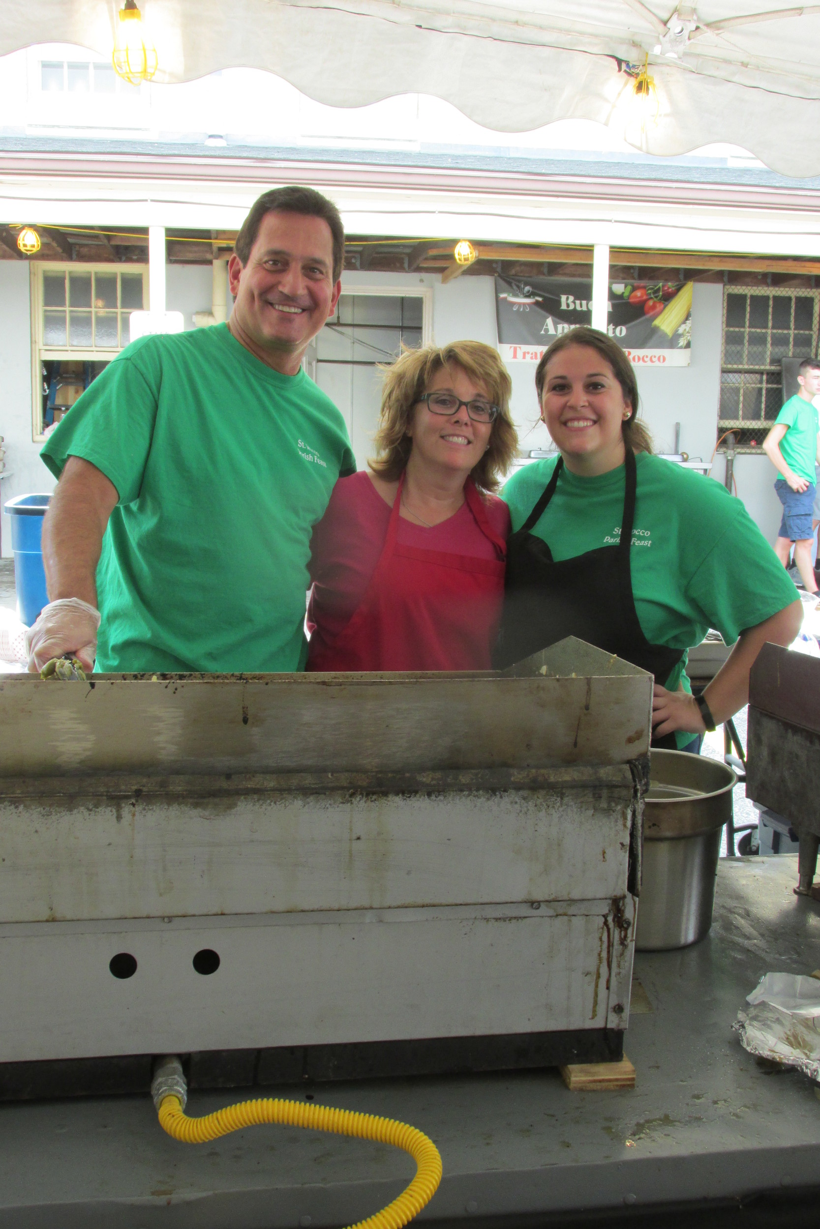 FAMILY FUN: The Montecalvo's – Mike, Marcia and Brianna – were among the many proud parishioners who helped make last weekend's Saint Rocco Feast and Festival a huge success. The famed WPRI-TV news anchor spent much of Saturday and Sunday cooking sausage and pepper sandwiches.