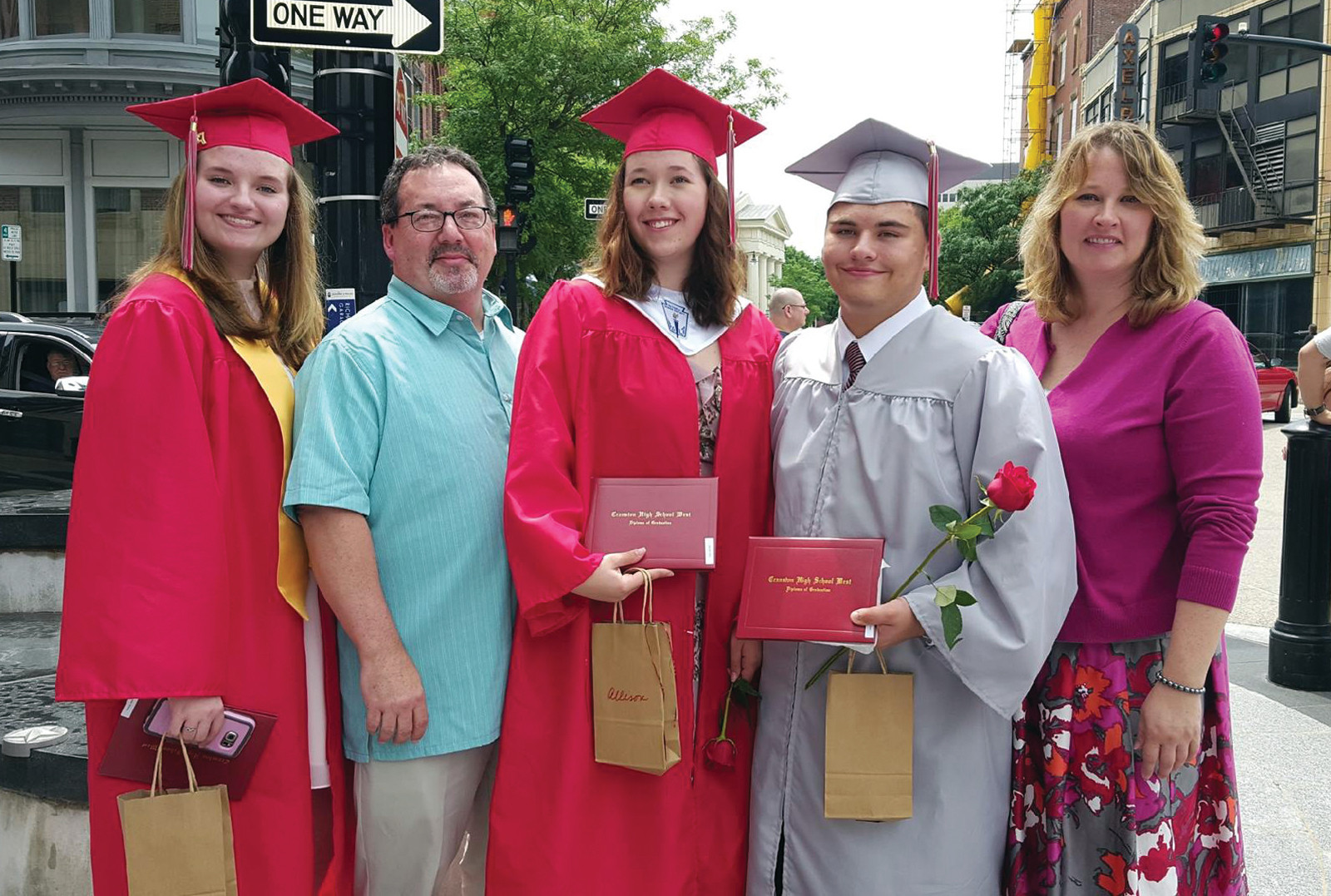 12 years of schooling have come to an end in Cranston for the triplets as they pose with Sue and Steve on graduation day.