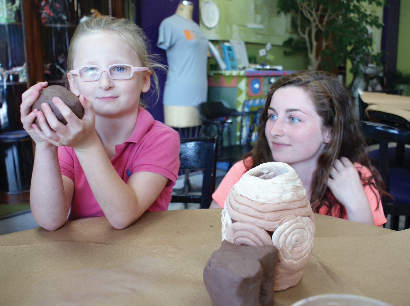 WITH GUIDANCE: Artists' Exchange instructor Sarah DeSimone looks on as Violet Umstadter, age 5, molds her clay at the most recent Craft Bash.