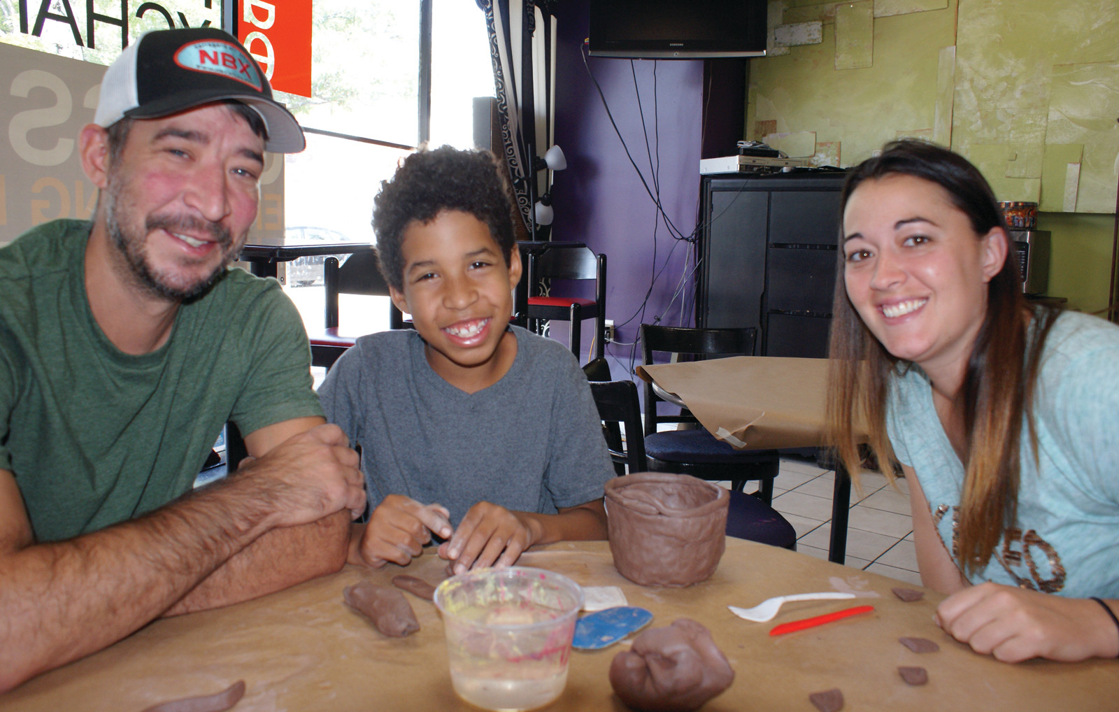 LEARNING TO WORK WITH CLAY: Kayden Johnson, age 9, learned how to work with clay at the Artists' Exchange's Craft Bash on Aug. 26. Pictured with Kayden are his father, Joshua Williams and his friend Kristen Muto.