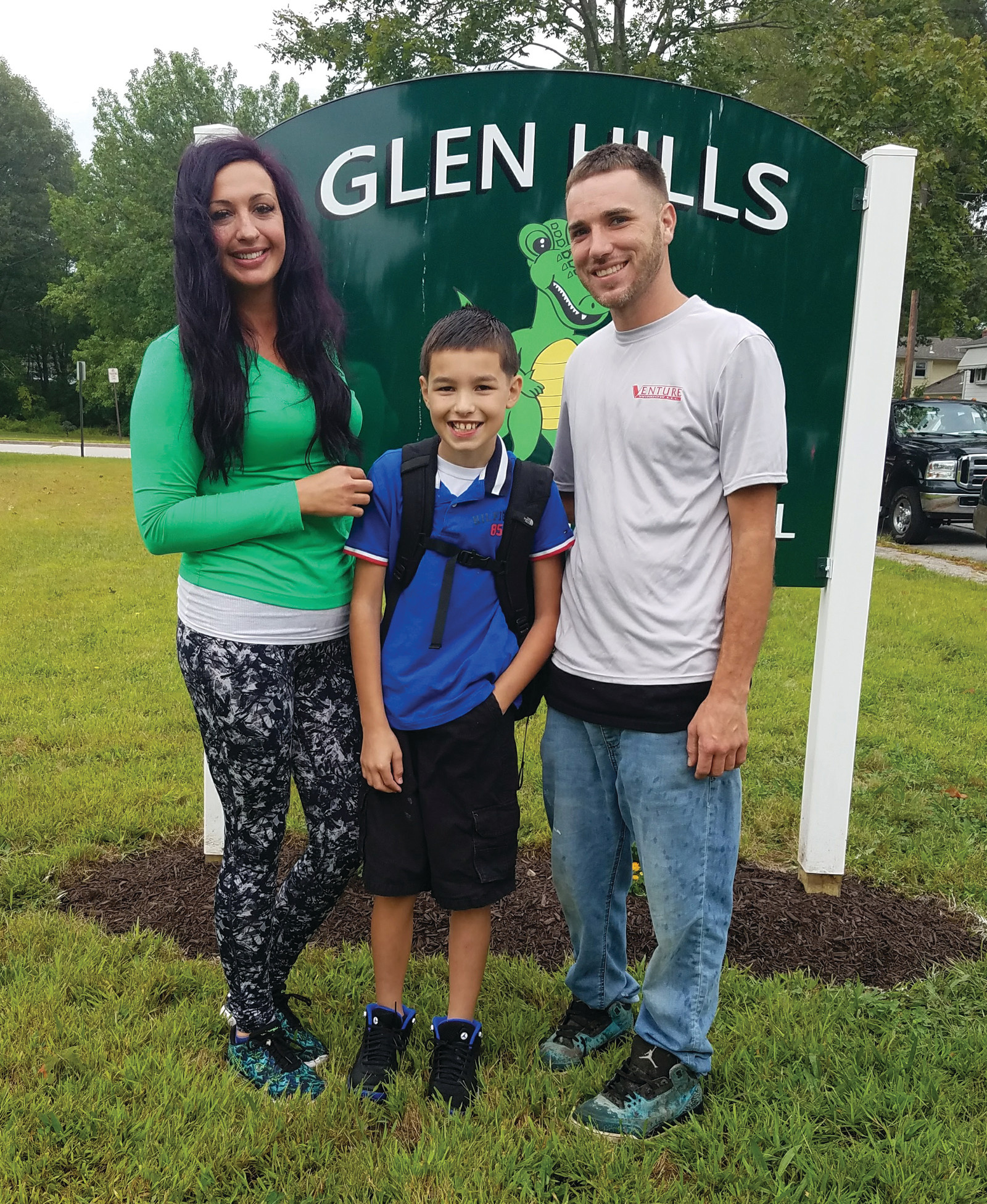 HEADING INTO THE FIFTH GRADE: Christopher Donnelly takes a moment to pose in front of the Glen Hills Gator sign at Glen Hills Elementary School during drop-off time on Tuesday morning. With him are James Donnelly and Heather Barber. (Herald photo by Jen Cowart)
