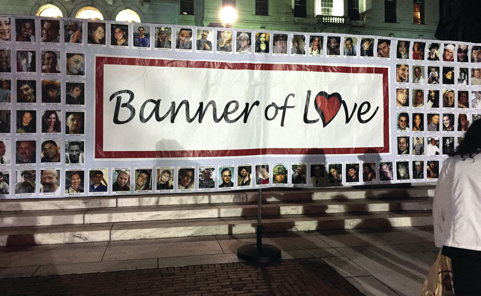 LOVE FROM ALL AROUND: The Banner of Love was raised on the steps of the State House in Providence on Thursday night, depicting pictures of those lost to overdose.