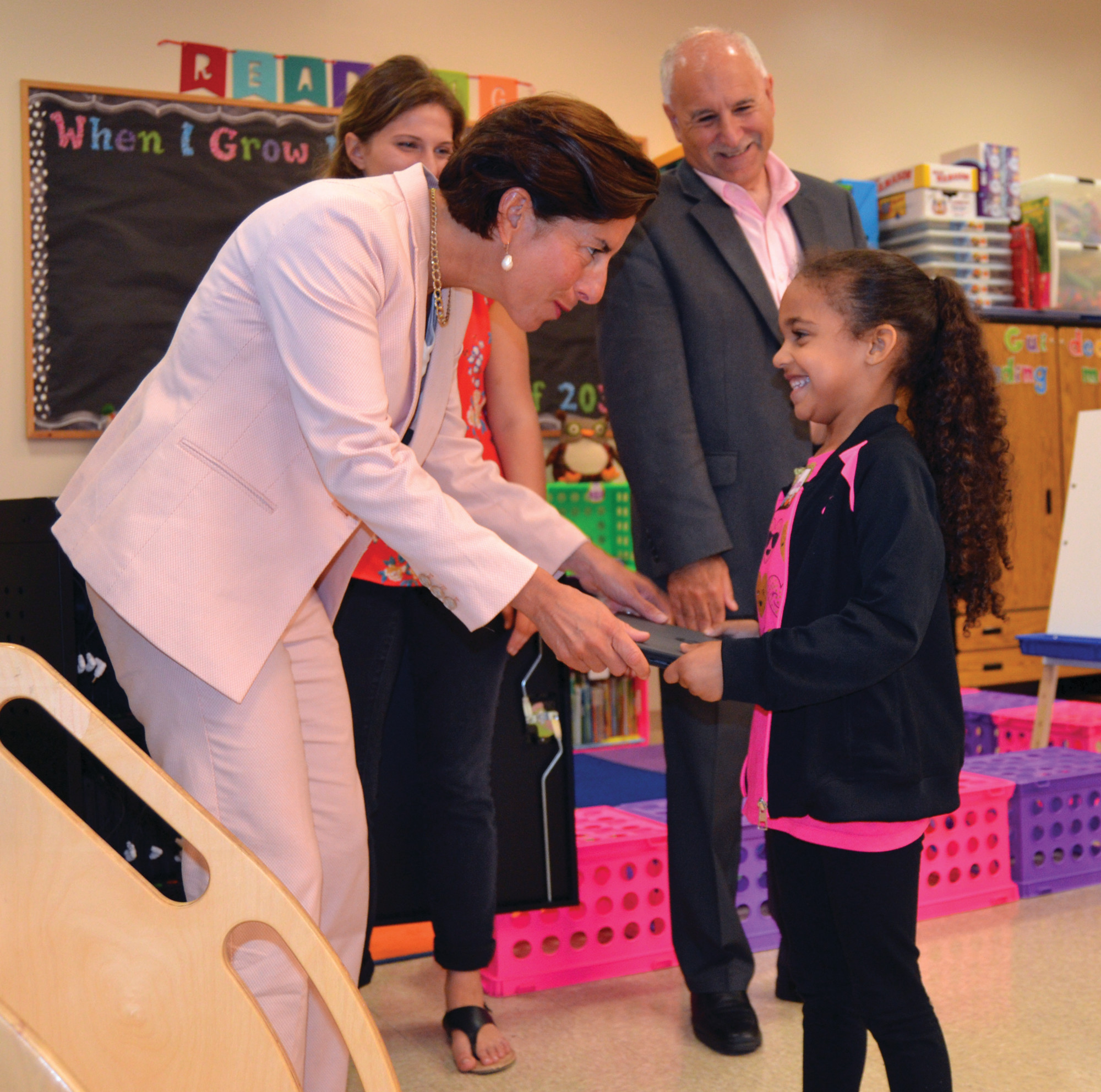 SMILES ALL AROUND: Angelina Mowrey, a kindergarten student at the ECC, receives her much-anticipated Google Chromebook from Gov. Gina Raimondo.