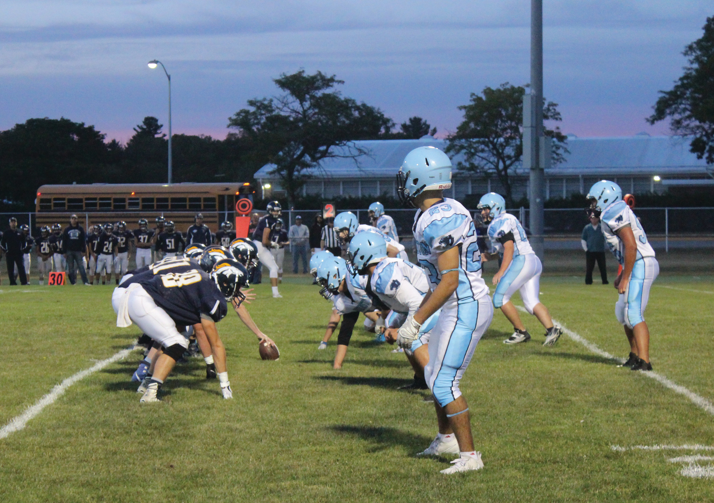SEASON UNDERWAY: Above, Johnston's defense waits on a Burrillville snap during Friday night's Injury Fund game at Smithfield.