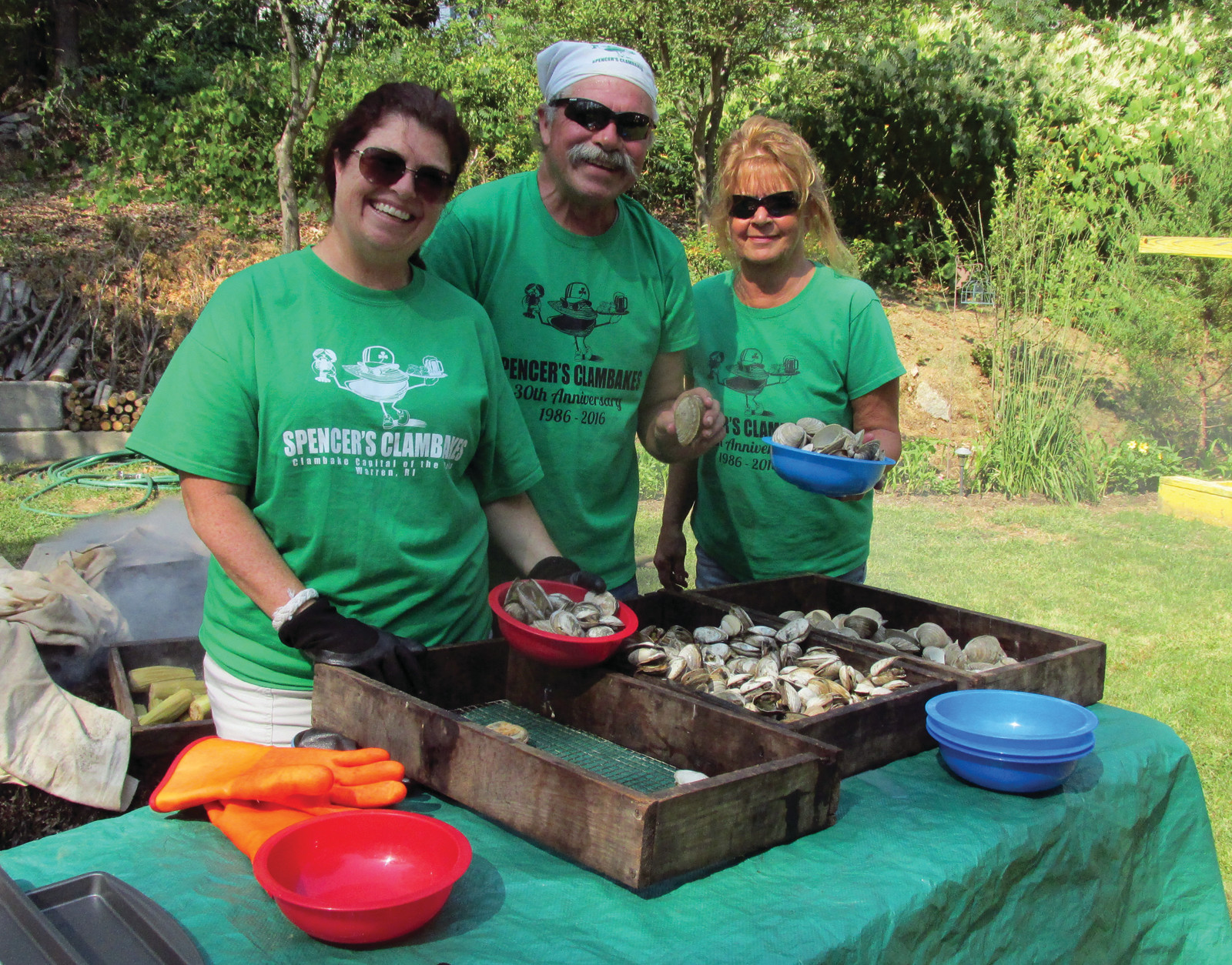 FAMILY FUN: The Hackley family – Kara, Spencer and Nancy – who own and Spencer's Clambakes, enjoy a lighter moment while they served steamers and little necks to people at Monday's special international clambake in Johnston.
