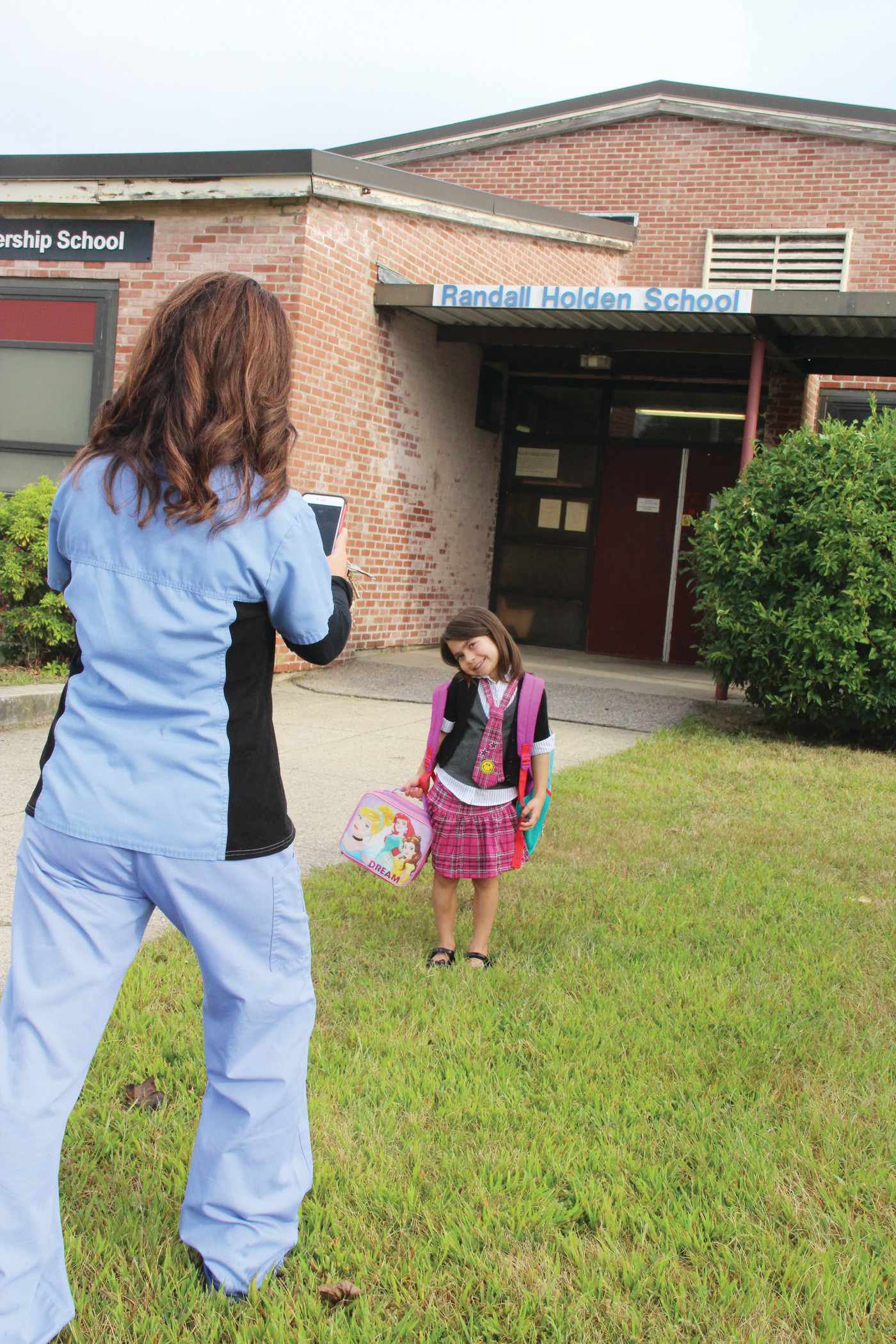 FIRST DAY OF K: Melissa DiRocco snaps a picture of her daughter, Natalia, as she's about to start her first day of kindergarten at Randall Holden School. The school is one of two slated to close next year with the consolidation of elementary schools. Wickes is the other with John Brown Francis becoming the early education center now at Drum Rock.