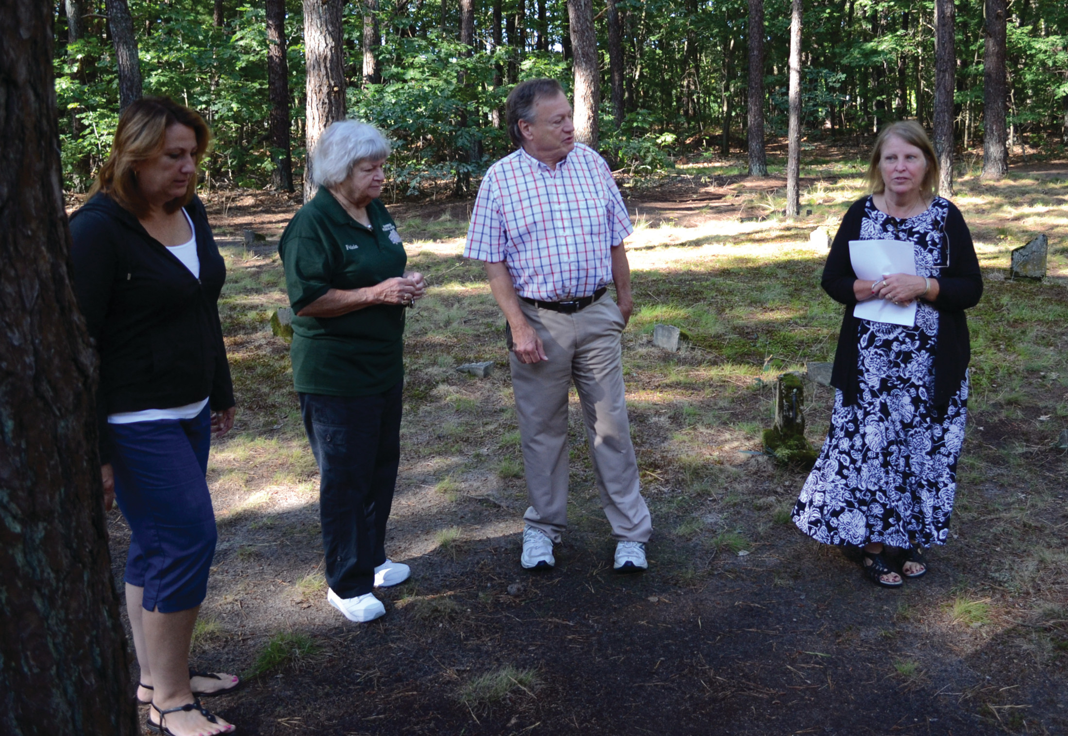 UNDER(CARE)TAKERS: Sue Cabeceiras, Felicia Gardella, Mark Brown and Pegee Malcolm stand inside Historic Lot #90 as they discuss their efforts to remember the approximately 100 people who were laid to rest there.