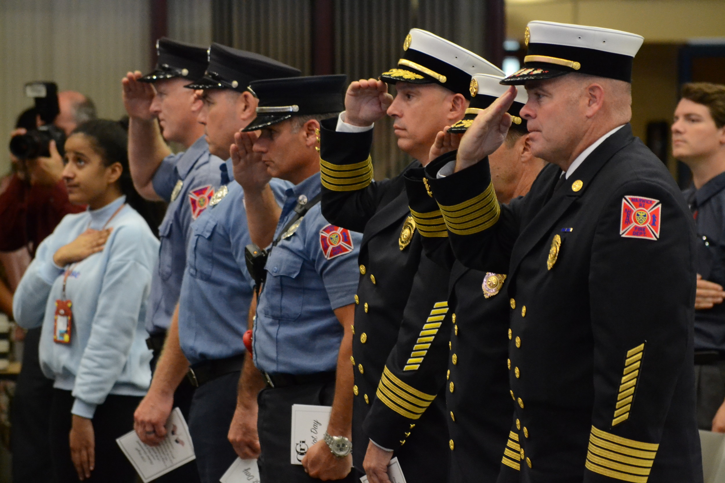 Members of the Warwick Fire Department salute during a bell ringing tribute at the CCRI event.