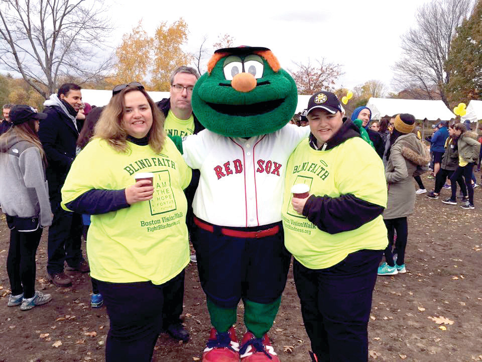 Heather (left) and Jeri (right) Schey pose with Wally the Green Monster at last year's Boston VisionWalk