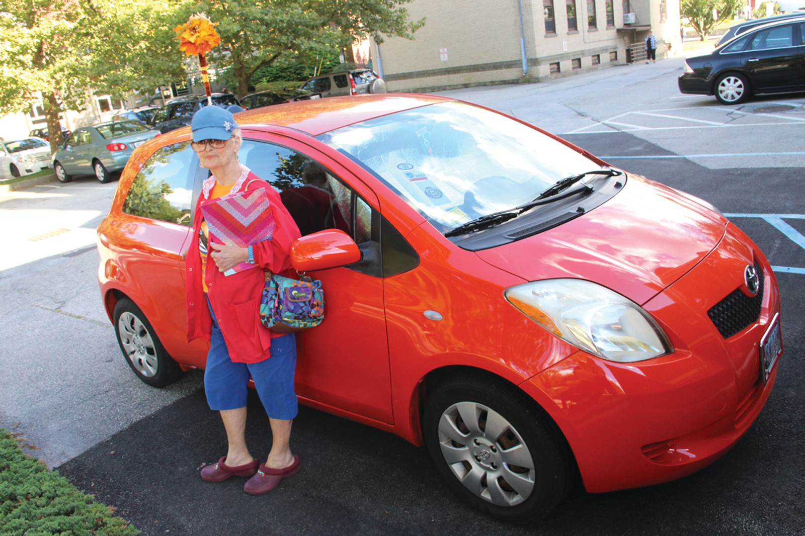Gloria Walker next to her brightly colored new car.