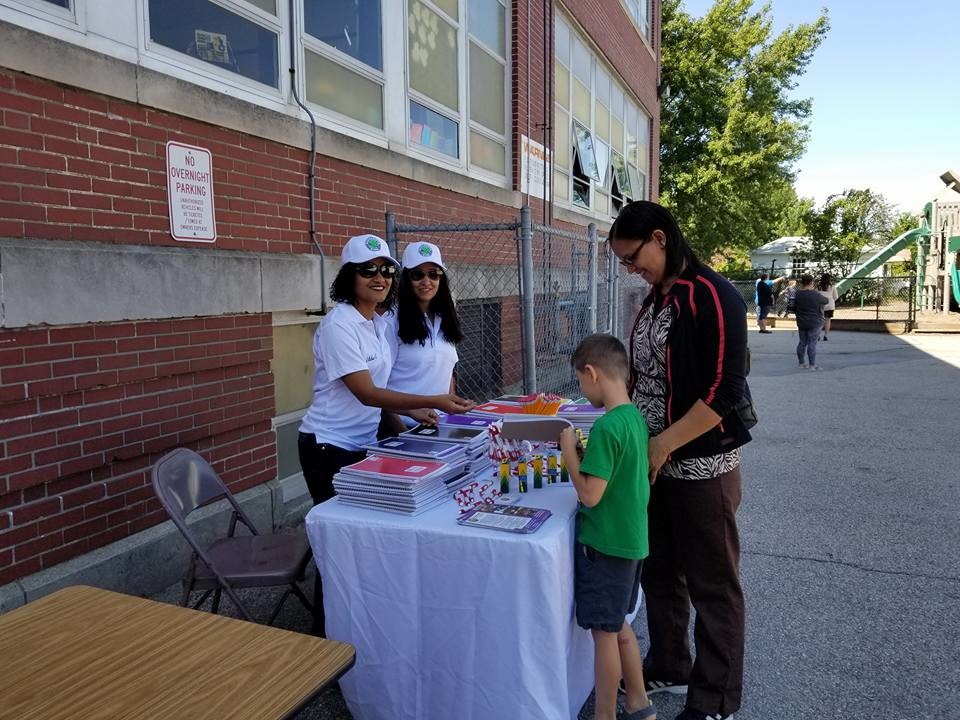 THERE'S ENOUGH FOR EVERYONE: From Esperanza-Hope Wilda Gutierrez and Glenda Hiciano pass out bonus school supplies to all students at the Chester Barrows Back to School event on September 1.