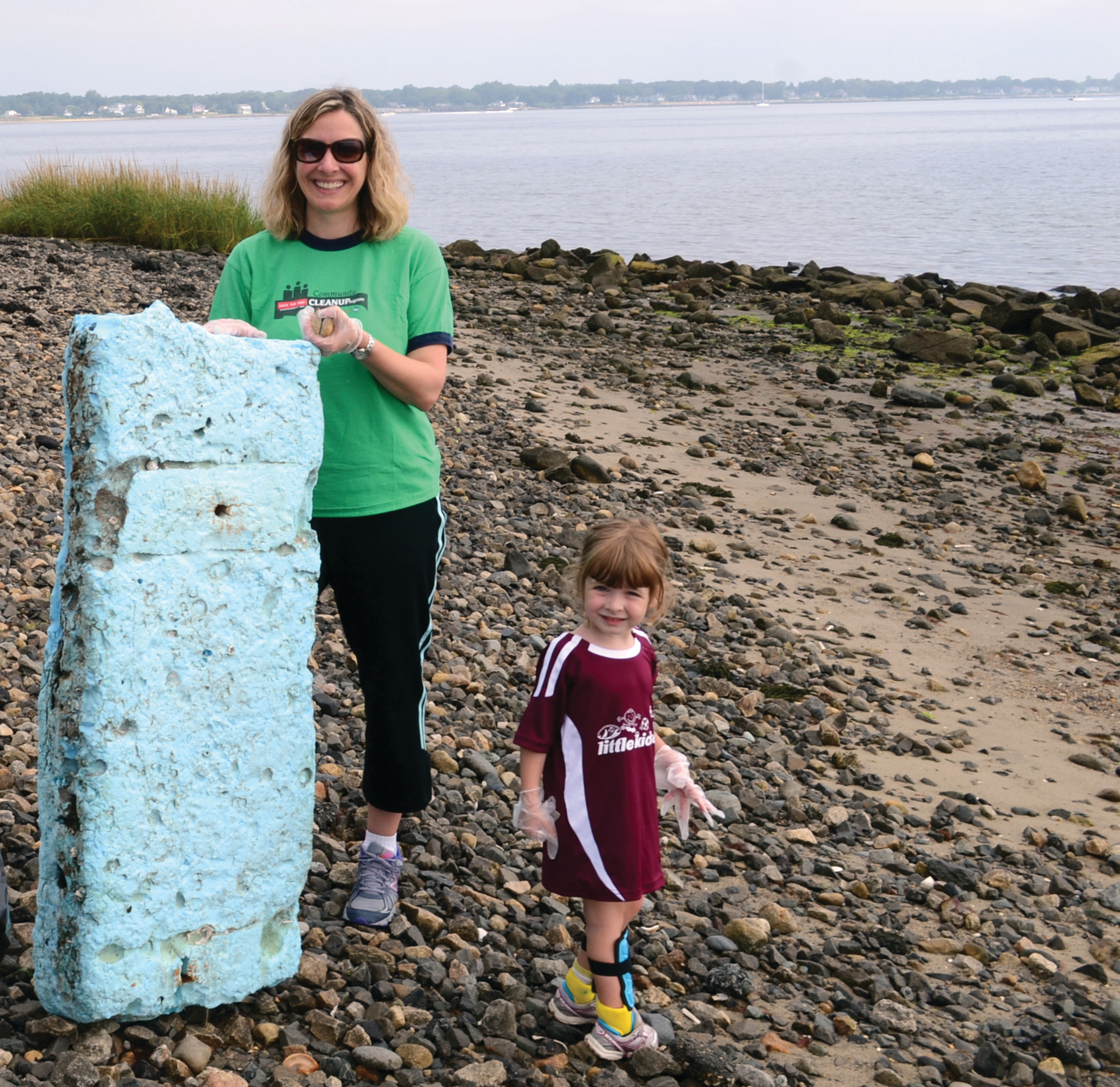 ALL HANDS ON DECK: Every individual, no matter how small, can help keep community shorelines clean, as evidenced by 3-year-old Sophie Murphy, pictured here with her mother, Xenia, on the shores of Chepiwanoxet Point.