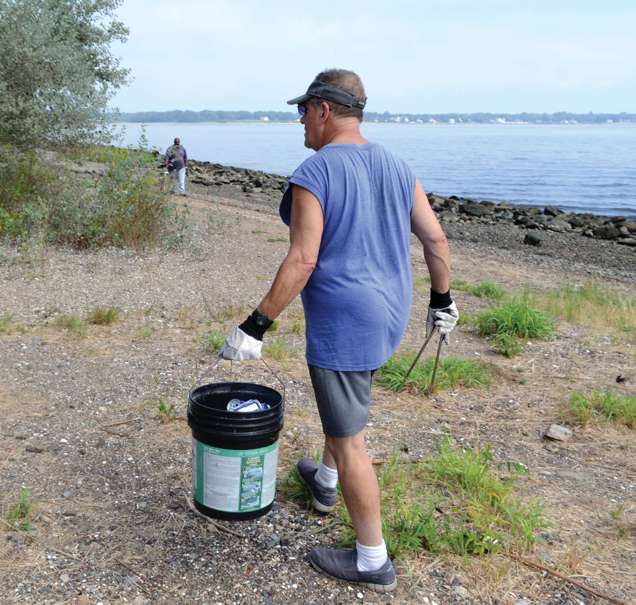 TAKE YOUR PICK: Jim DeAmbrosia scours the beaches of Chepiwanoxet Point with a bucket and a pair of salad tongs, which he finds to be the most effective tool for removing garbage.