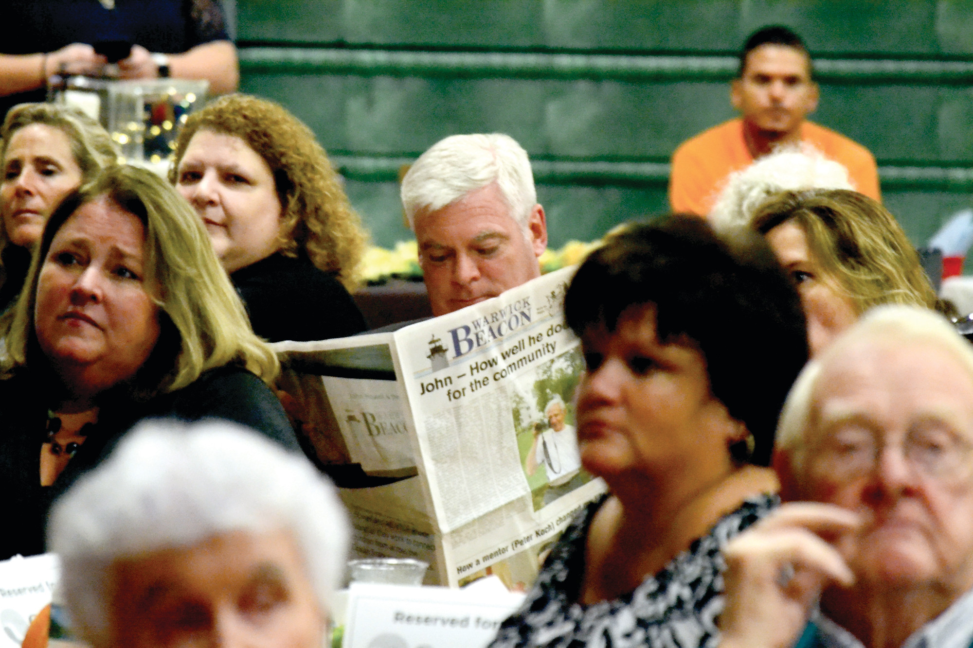 EXTRA EXTRA: Mayor Avedisian sits absorbed in the special edition of the Beacon that was produced especially for John Howell's tribute event, held at Bishop Hendricken last Thursday evening.