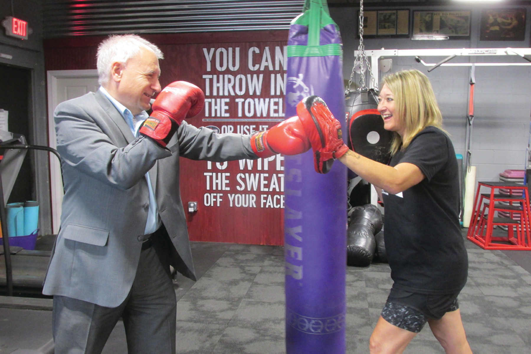 POWER PUNCH: Johnston Mayor Joseph Polisena tests his mettle during a fun-filled exchange with Christina Rondeau, the popular owner-operator of Rondeau's Kickboxing and Fitness that has moved to 609 Killingly Street and held its Grand Opening Saturday.
