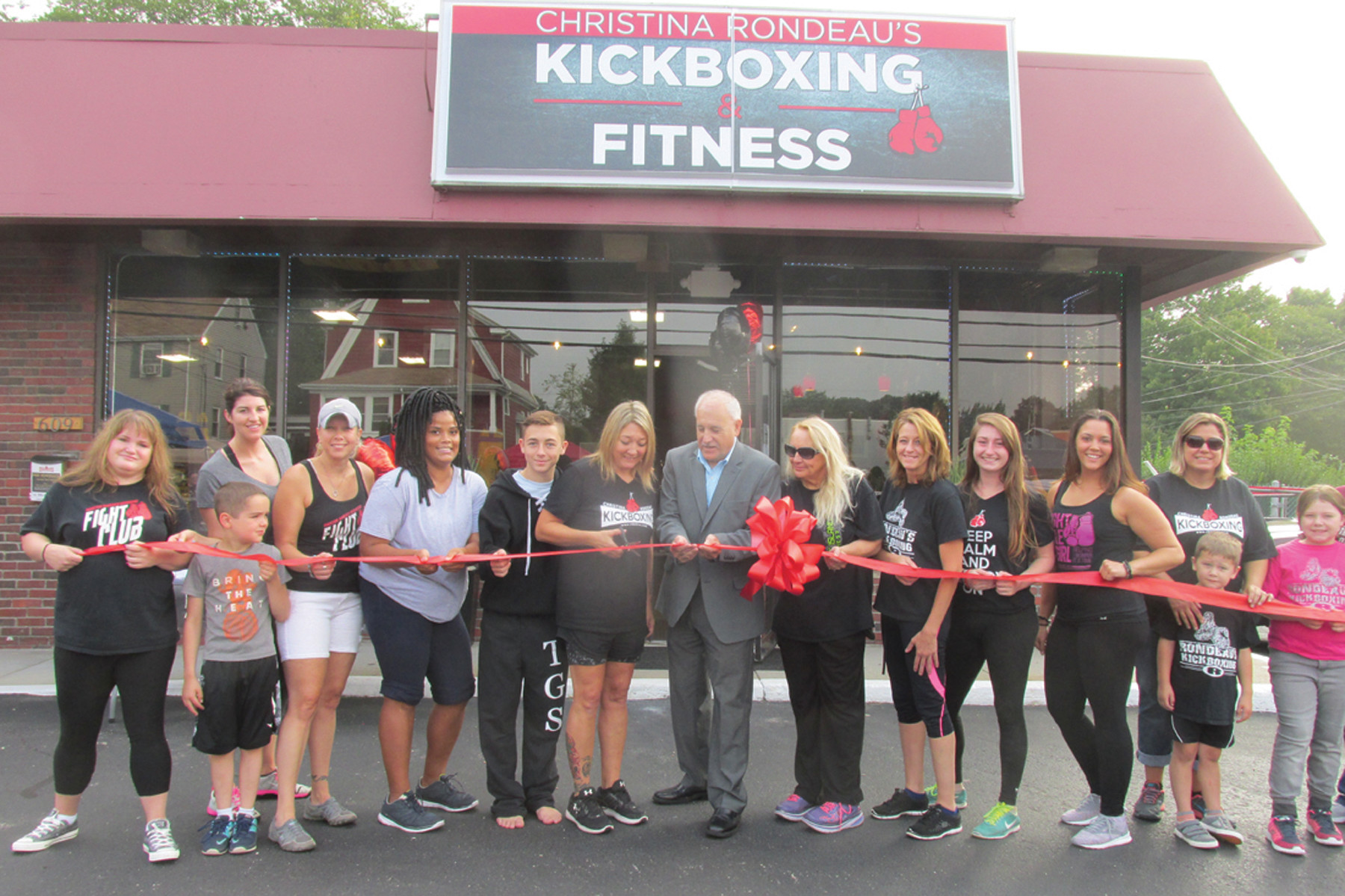 SUPER STAFF: The expert staff of Rondeau's Kickboxing and Fitness joined owner Christina Rondeau and Mayor Joseph Polisena for Saturday's official opening of her new location at 609 Killingly Street.