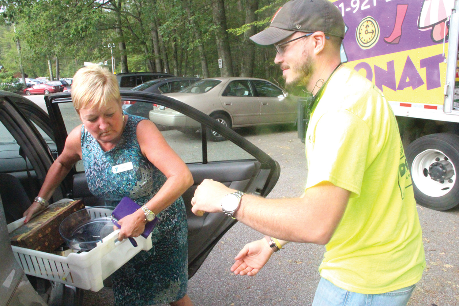 CURBSIDE SERVICE: Kent County YMCA director of operations Julie Casimiro and James Juskalian of Big Brothers Big Sisters unload donations dropped at the Y Wednesday morning.