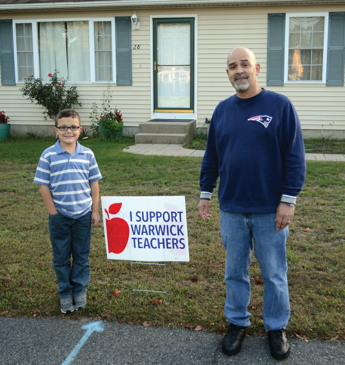 SIGN OF SUPPORT: Michael Pella-Sabourin and his son, Matthew, stand on either side of one of the lawn signs that he ordered to hand out to his neighbors as a show of support for Warwick's teachers. The movement has grown steadily since its humble beginnings.
