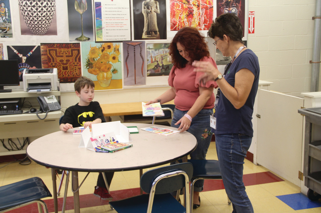 LOOKING OVER THE WORK: JBF Principal Michelle Depot (center) looks over student work with substitute art teacher Joanne Longo. Still working on his drawing is Ryan Nicolaides.
