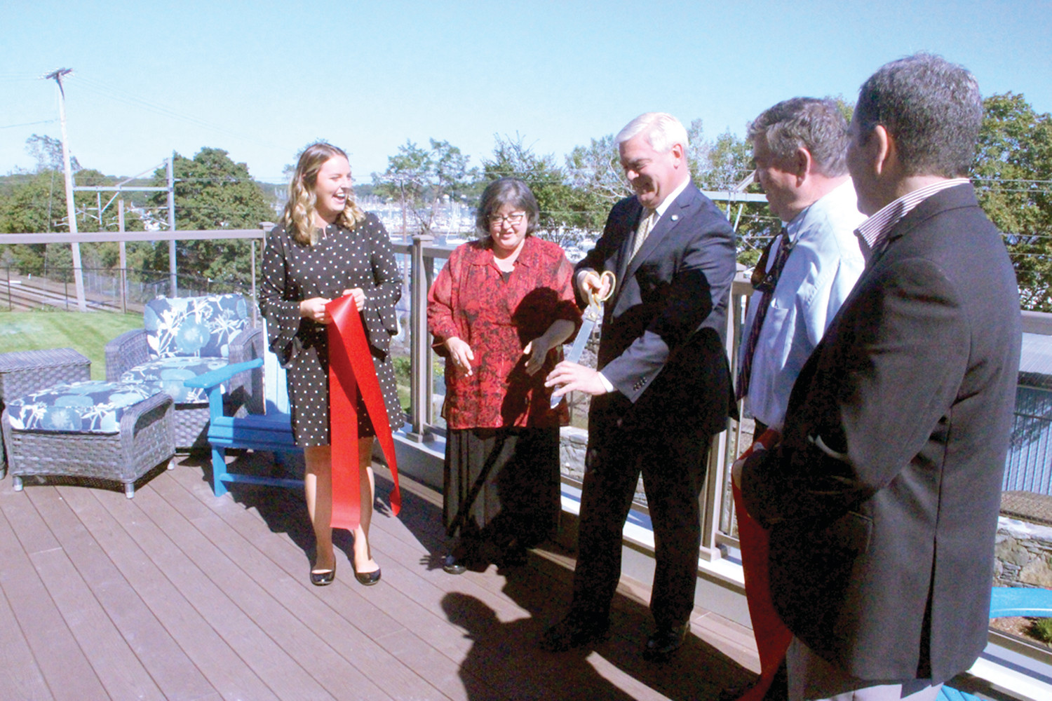 HANDING BACK THE SNIPS: The Miga family, staff of Brentwood by the Bay Assisted Living and guests joined on the terrace overlooking Greenwich Bay on Wednesday for the official opening of the facility in Cowesett. Here, Mayor Scott Avedisian hands back the scissors following the ribbon cutting.