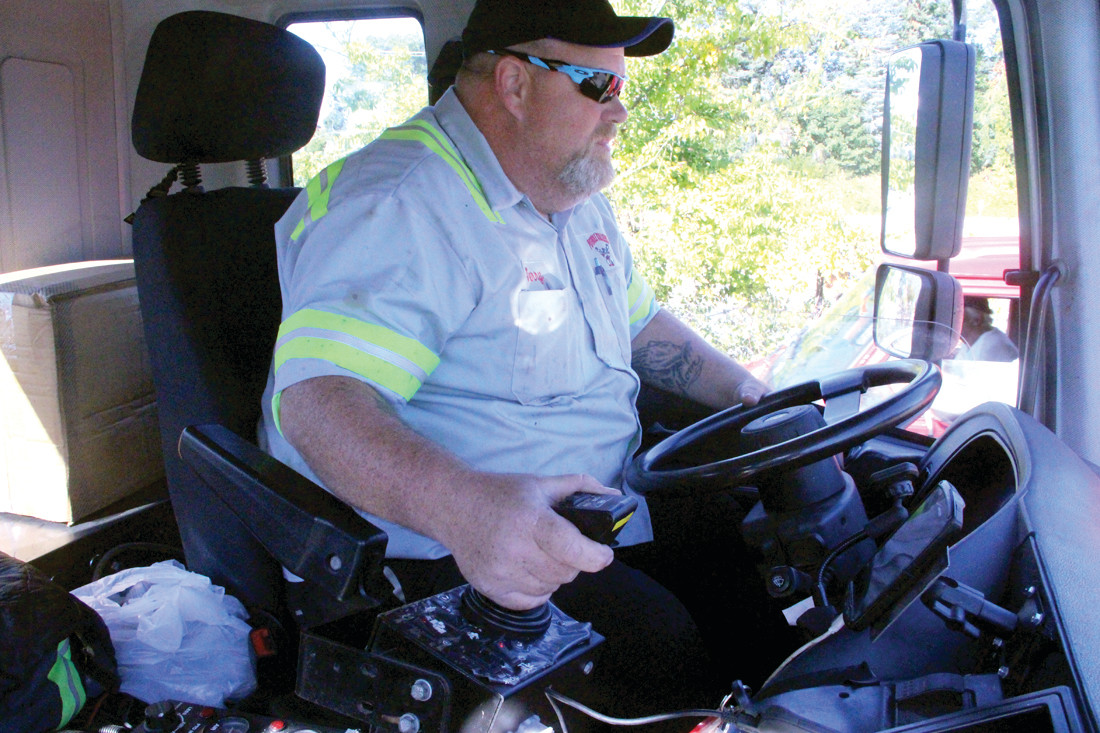 "ALL WITH A TOUCH OF THE HAND: Using a ""joy stick,"" Jerry Lambert fills a pothole without leaving the cab of the truck."