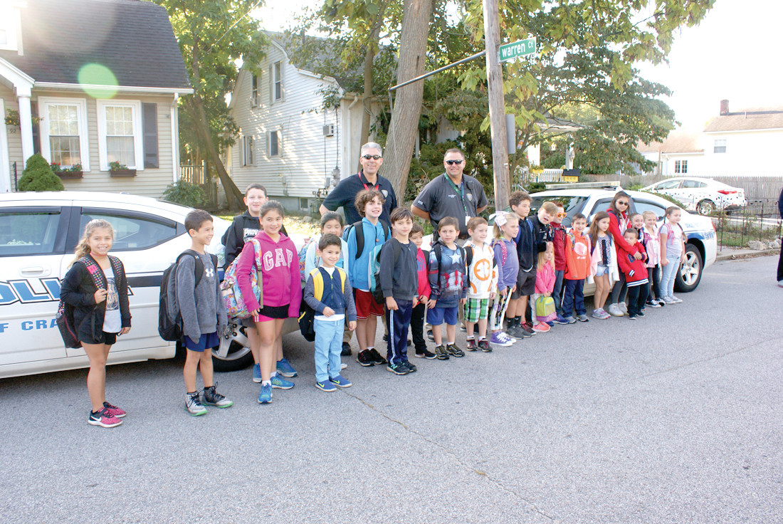 READY TO WALK: Pictured are Cranston Police SROs Matt Davis and Derek Dimeo, who led the International Walk to School Day to Oaklawn    Elementary. They are pictured with some of the students who participated.