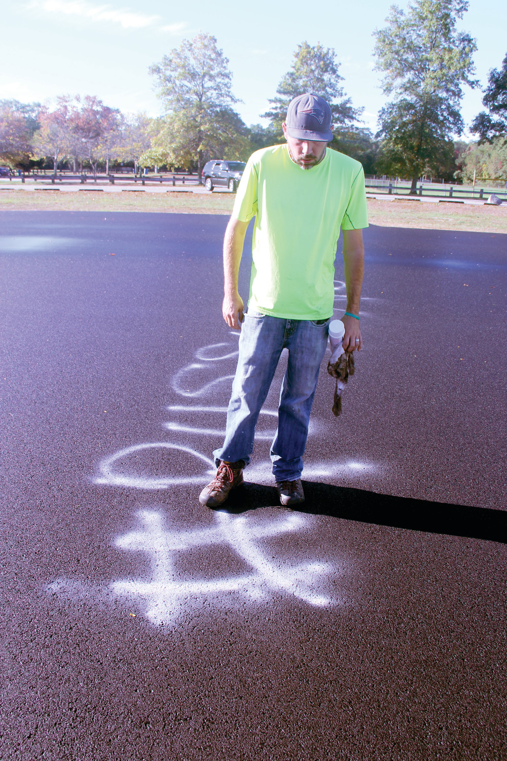 The recently completed surface for a new in-line skating rink at City Park was the target of vandalism over the weekend. Tom McGovern of the Department of Public Works assesses the damage that will be painted over.