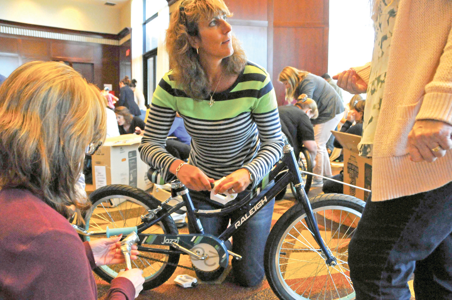 ALL ABOUT TEAMWORK: Employees from Citizen's Bank work on assembling a bike.