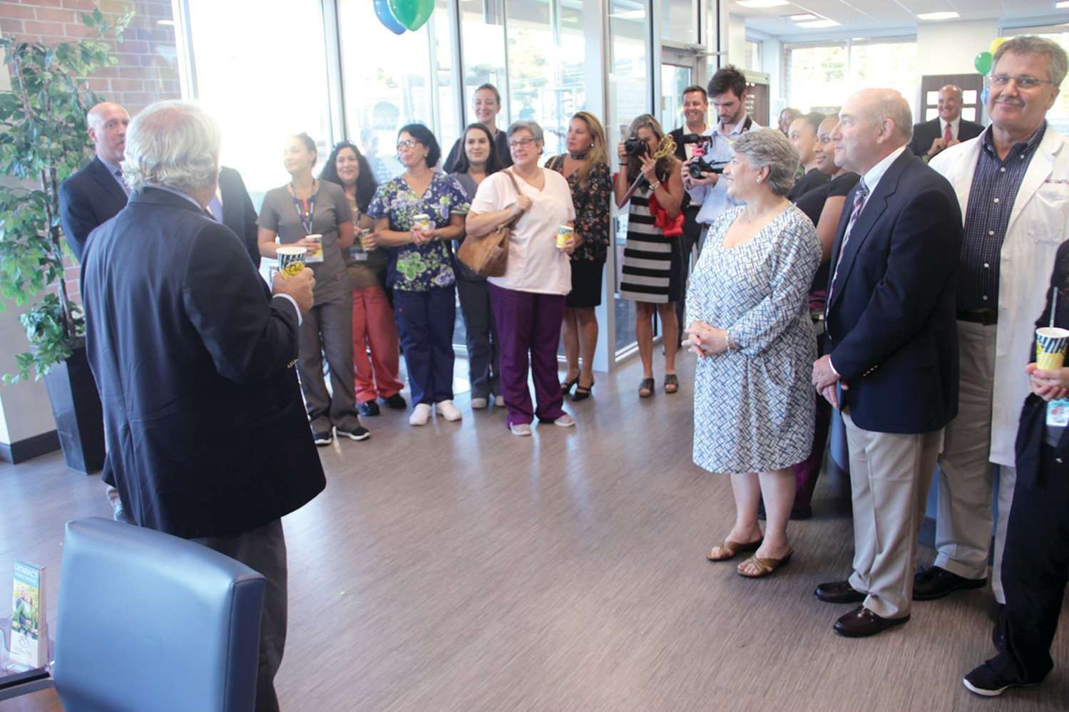 MANY YEARS, MANY FRIENDS: Dr. Paul Koch addresses staff, friends and family who attended the formal opening of the new Koch Eye Associates office on Greenwich Avenue.