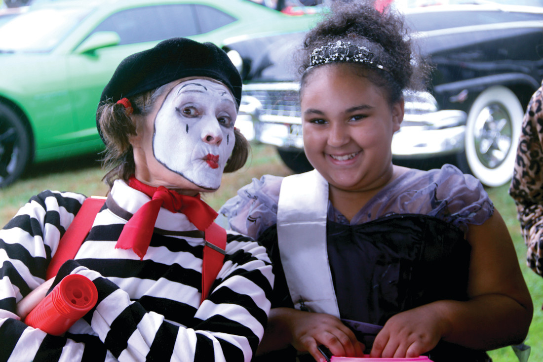 BALLOON ANIMALS: Amy the Mime created balloon animals, not to mention some great expressions, for kids and adults attending the pre-Halloween and cruise car event hosted by the Warwick Lions Club. Here, she is with Nevaeh Lewis.