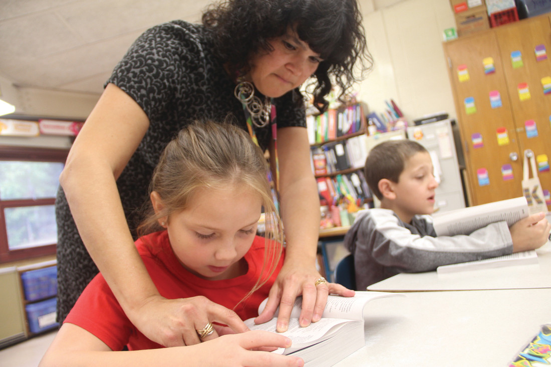 LOOKING A WORD UP: Scott School third grade teacher Kimberly Kane assists Summer Monteiro in looking up a word in her new dictionary.
