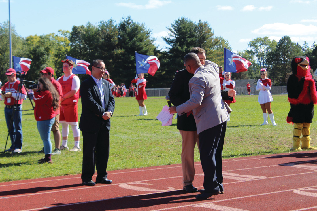 AN EMOTIONAL DAY: Principal Tom Barbieri offers a hug to Dr. Andrew Lemoi, son of former Principal Ed Lemoi as a special rock was unveiled, painted in honor of the former principal.