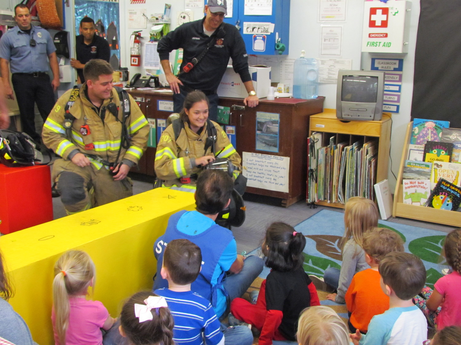 GEARED UP TO BE SAFE: Firefighters Andrew Kazarian and Victoria Bellavance show their gear to the Y's Owl Nursery School students.