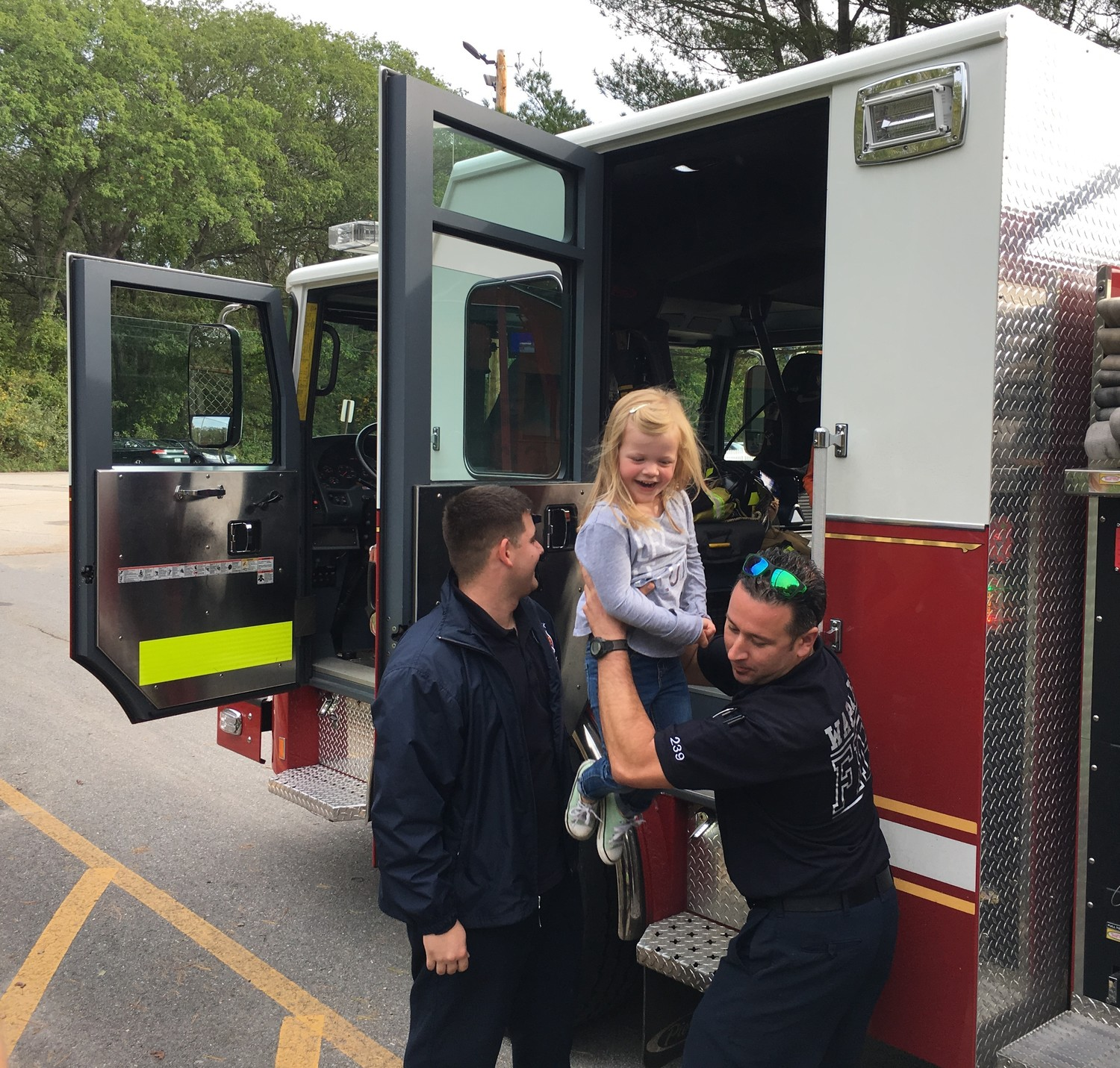 A LIFT: Firefighters Andrew Kazarian and Anthony Delpozzo give Chloe Slezak a lift off the fire truck.