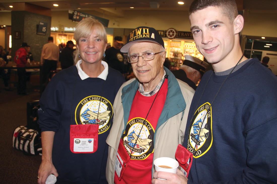 A PAIR OF GUARDIANS: Jacquelyn Walton, who works at McShawn's Pub that has helped sponsor many of the honor flights, was excited to serve as guardian for Louis Giarrusso, 94, of Cranston along with Brendan Morgan. Drafted at age 19, Giarrusso served in the Army in the infantry as a rifleman in the South Pacific. After the war under the GI Bill he attended Johnson & Wales College and then had a 39-year career with General Electric where he worked in computer development.