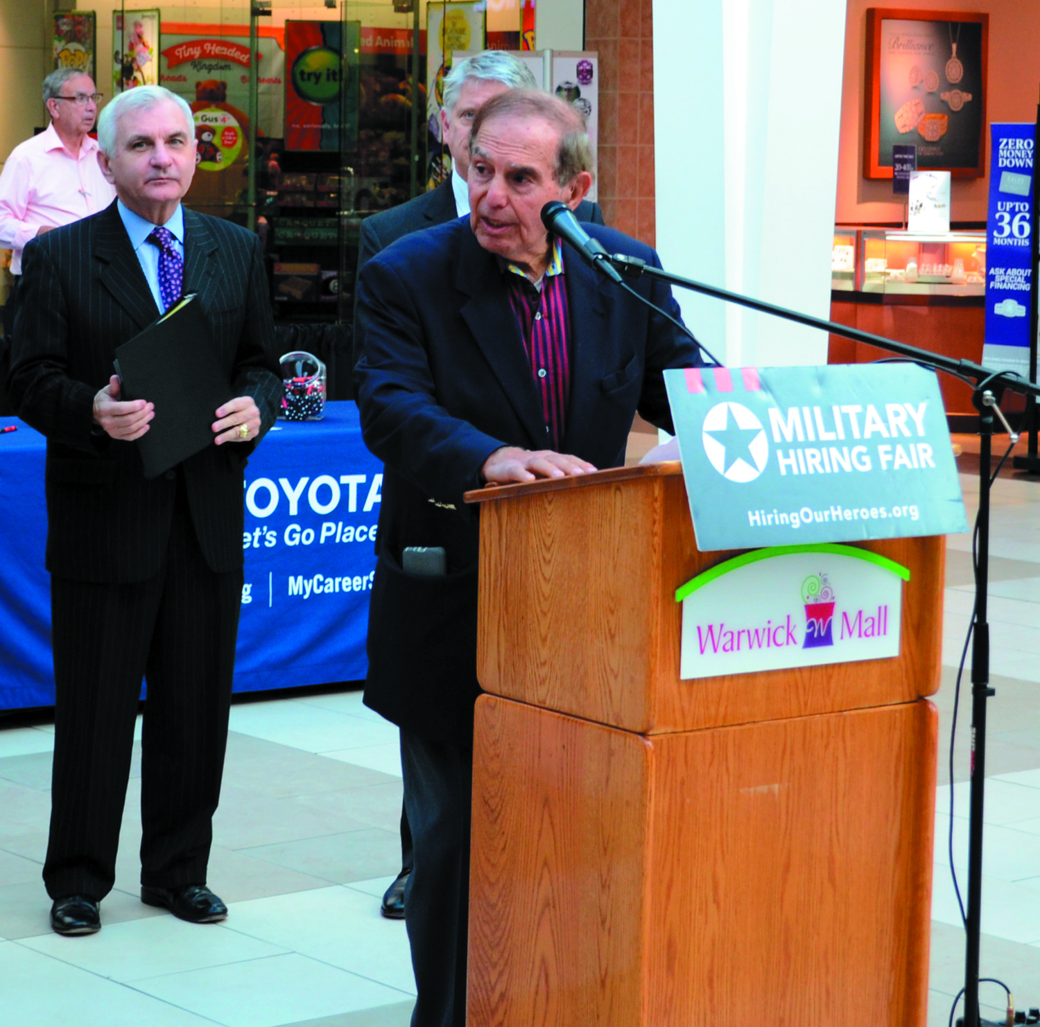 A NEW HOME FOR HIRING: Managing partner of Warwick Mall Aram Garabedian speaks to a crowd prior to the official kick-off of the Hiring Our Heroes professional job fair. Senator Jack Reed is behind him.
