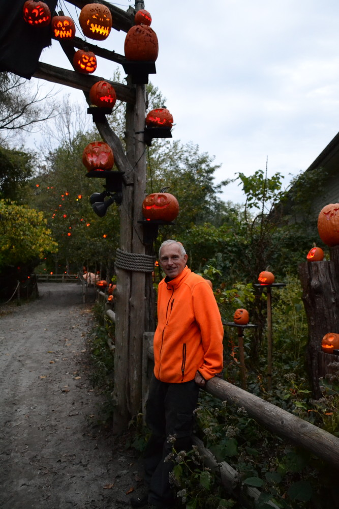 Reckner, sporting an appropriately orange jacket, poses along the festive path of his creation.