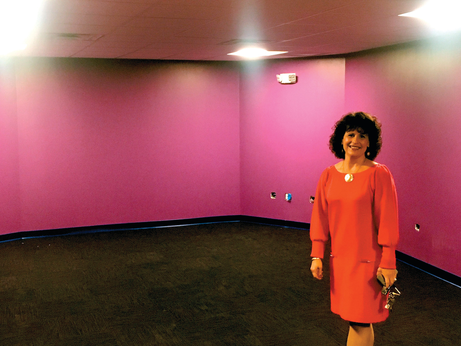 HAPPY COLORS: Boys & Girls Club of Warwick executive director Lara D'Antuono stands in the room that was once a shooting range for the Army Reserve, and will soon be home to a different kind of music – a full band in fact. The purple room will be the new home for a full, soundproof recording studio.