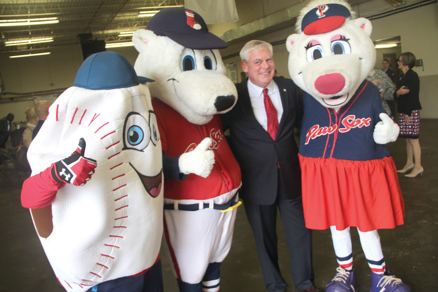 HIS FANS: Mayor Scott Avedisian is greeted by the PawSox mascots at Tuesday's kickoff of Operation Holiday Cheer. Avedisian joked he was negotiating for the Pawtucket Red Sox stadium to be built in Warwick.