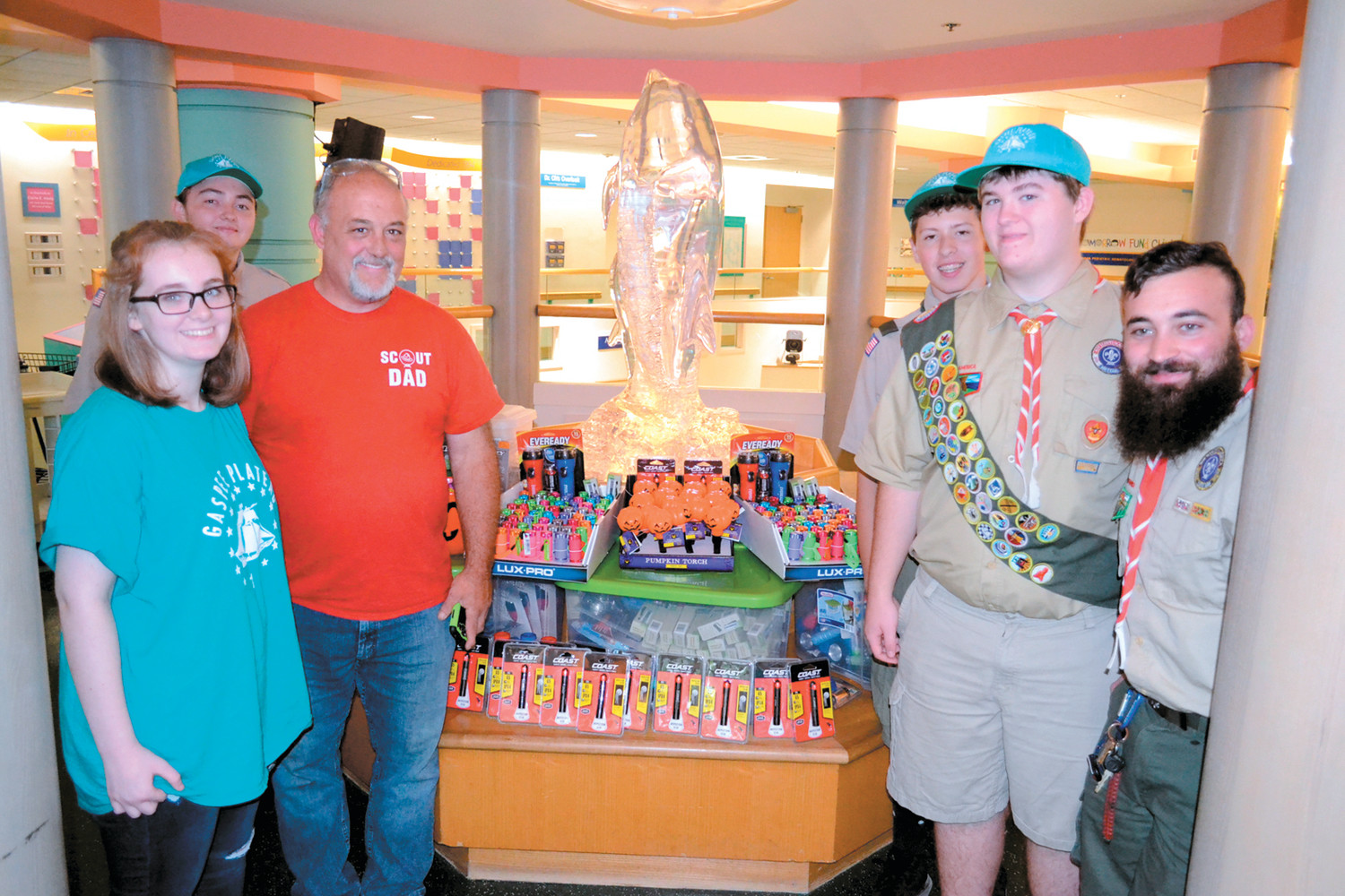 GUIDING LIGHTS: Eion Daniels (right middle) and his fellow Scouts Mitchell Carvalho (left middle), Ben McQuade (right, rear) and David Tibbitts (right front), his sister Mollee and father Tom prepare the flashlights for Hasbro staff on Thursday afternoon.