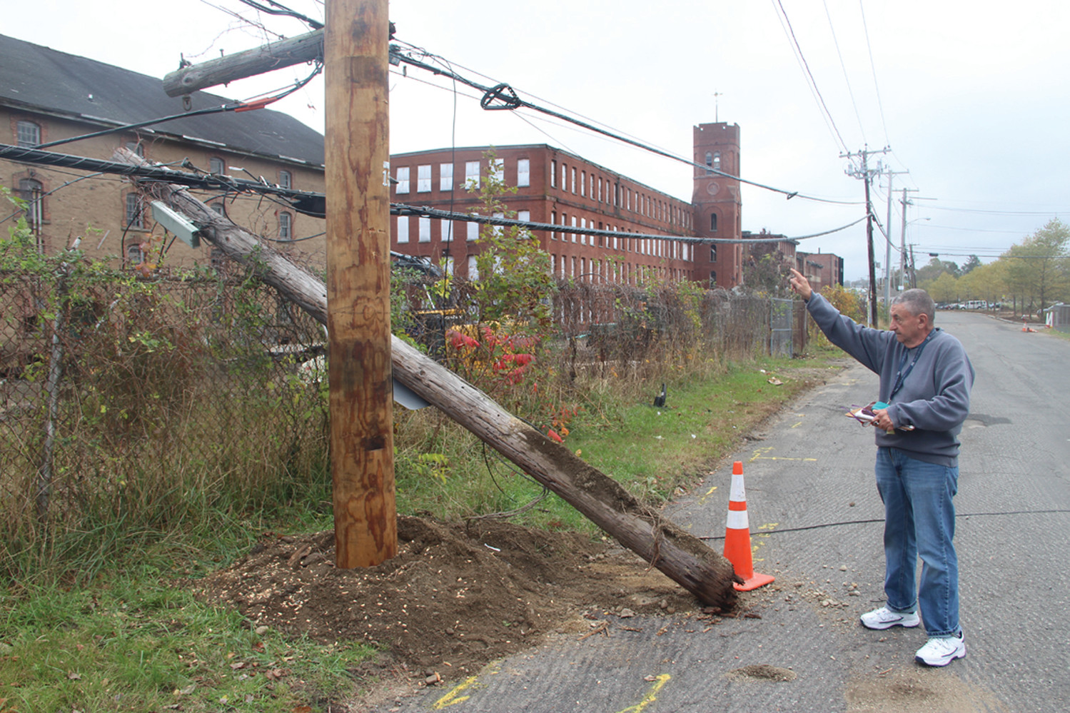 SCENE OF INCIDENT: Joseph DeFranco points to the utility pole on Knight Street that he says was split when a vehicle working on the former Pontiac Mills property snagged a wire.