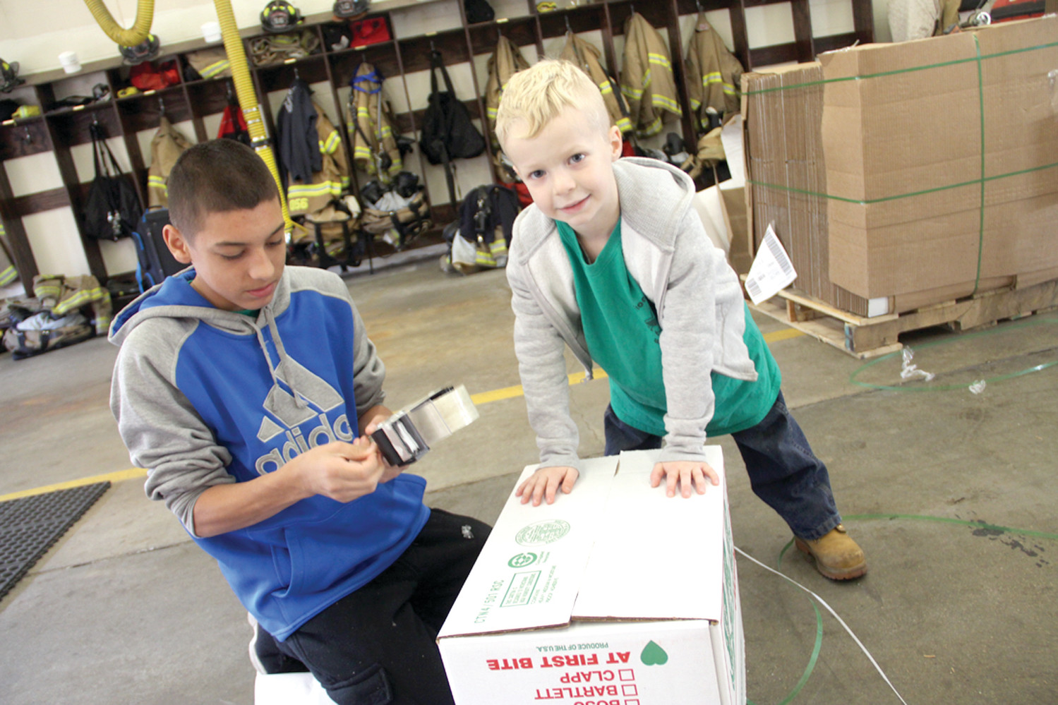 THE BOX CREW: Marcus Pascual and Julius Saint Butler prepare boxes for the food collection last Saturday at the fire station at the intersection of Sandy Lane and West Shore Road.