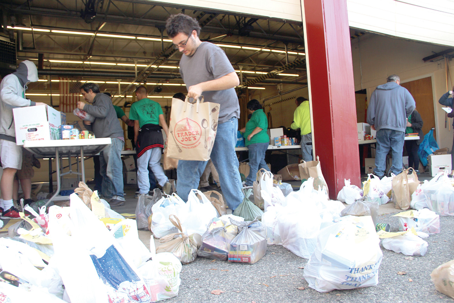 A BUSY PLACE: Scouts from Warwick Troop 63, their parents and volunteers sorted and boxed food donations at the fire station serving as the collection point for Conimicut, Bayside, Warwick Neck and other close by neighborhood.