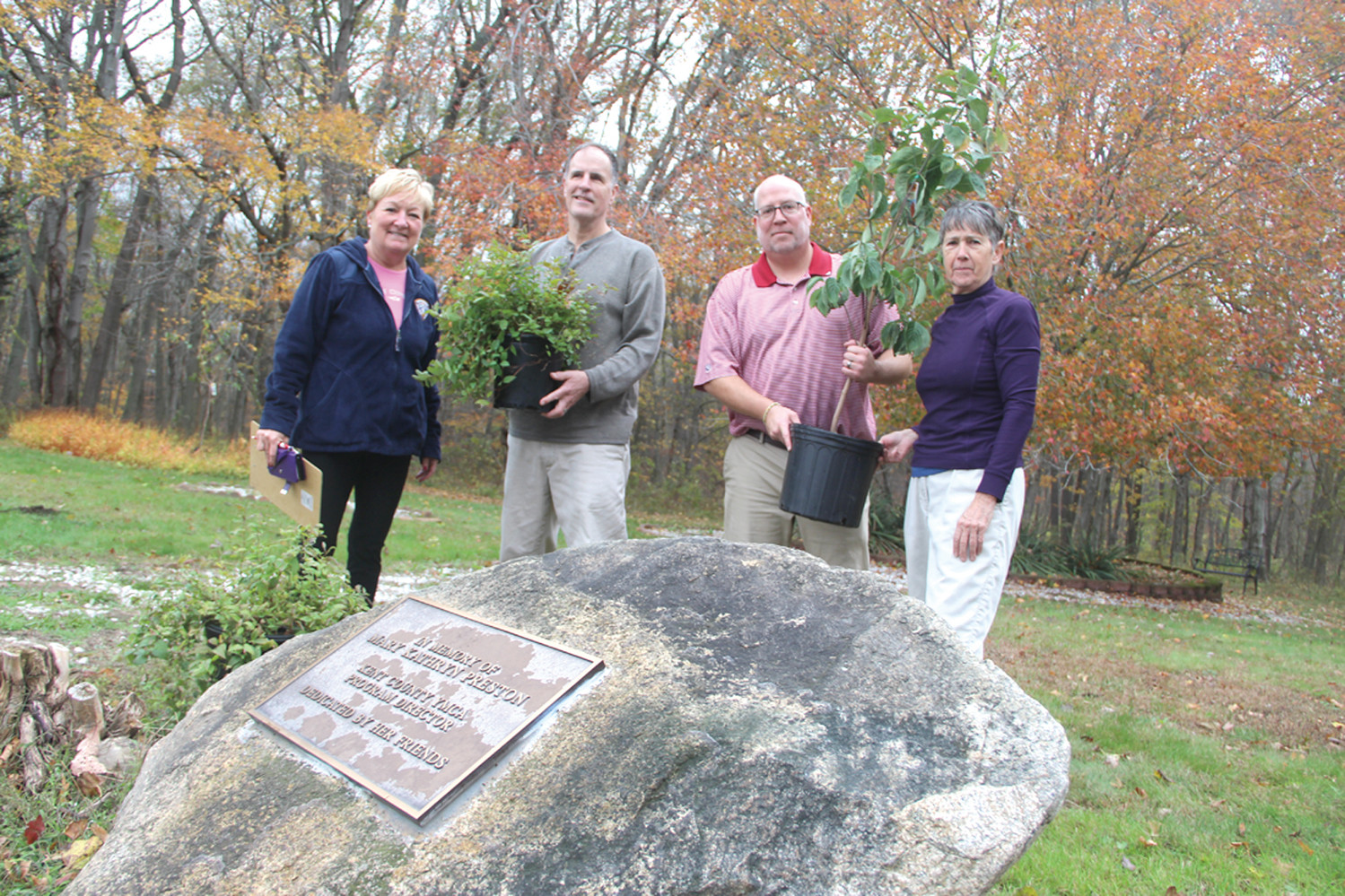 REMEMBERING TWO MARYS: Thanks to the donations of plants and shrubs from Laura LaBossiere, several sections of the Kent County YMCA grounds including the Mary K. Preston memorial garden will have flowering dogwoods and shrubs. Pictured from left are Kent Y director Julie Casimiro, Christopher Bourque, Ian McDermott of the Y and Laura LaBossiere. As the garden was beautified, the group also remembered Mary's mother, Mary B. Preston, who died Nov. 3.