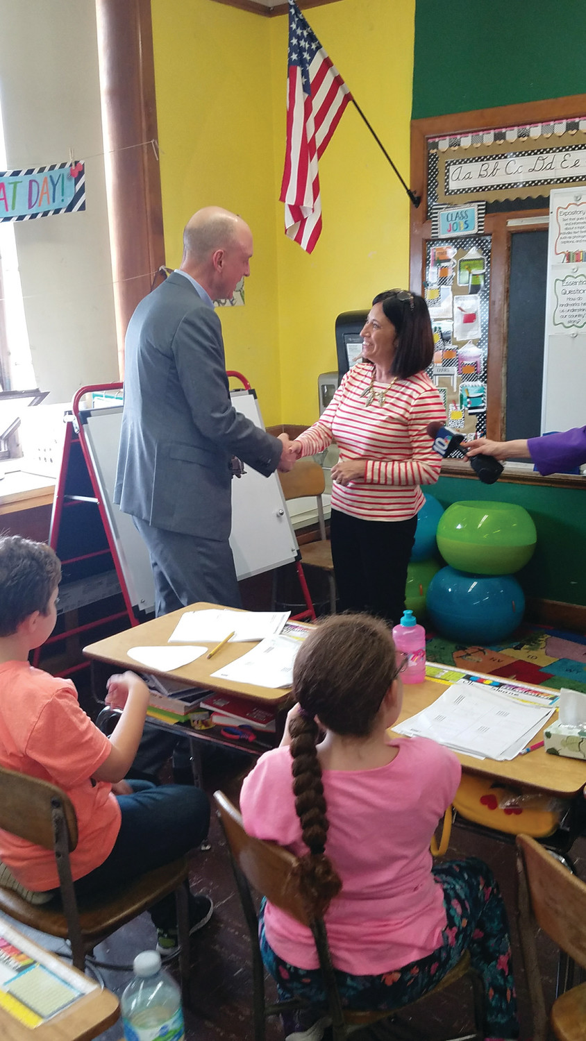 PROUD TO HAVE YOU ON OUR TEAM: Rhode Island Department of Education's Commissioner Ken Wagner congratulated Soccio on her accomplishments and thanked her for a job well done, presenting her with the official Golden Apple award.