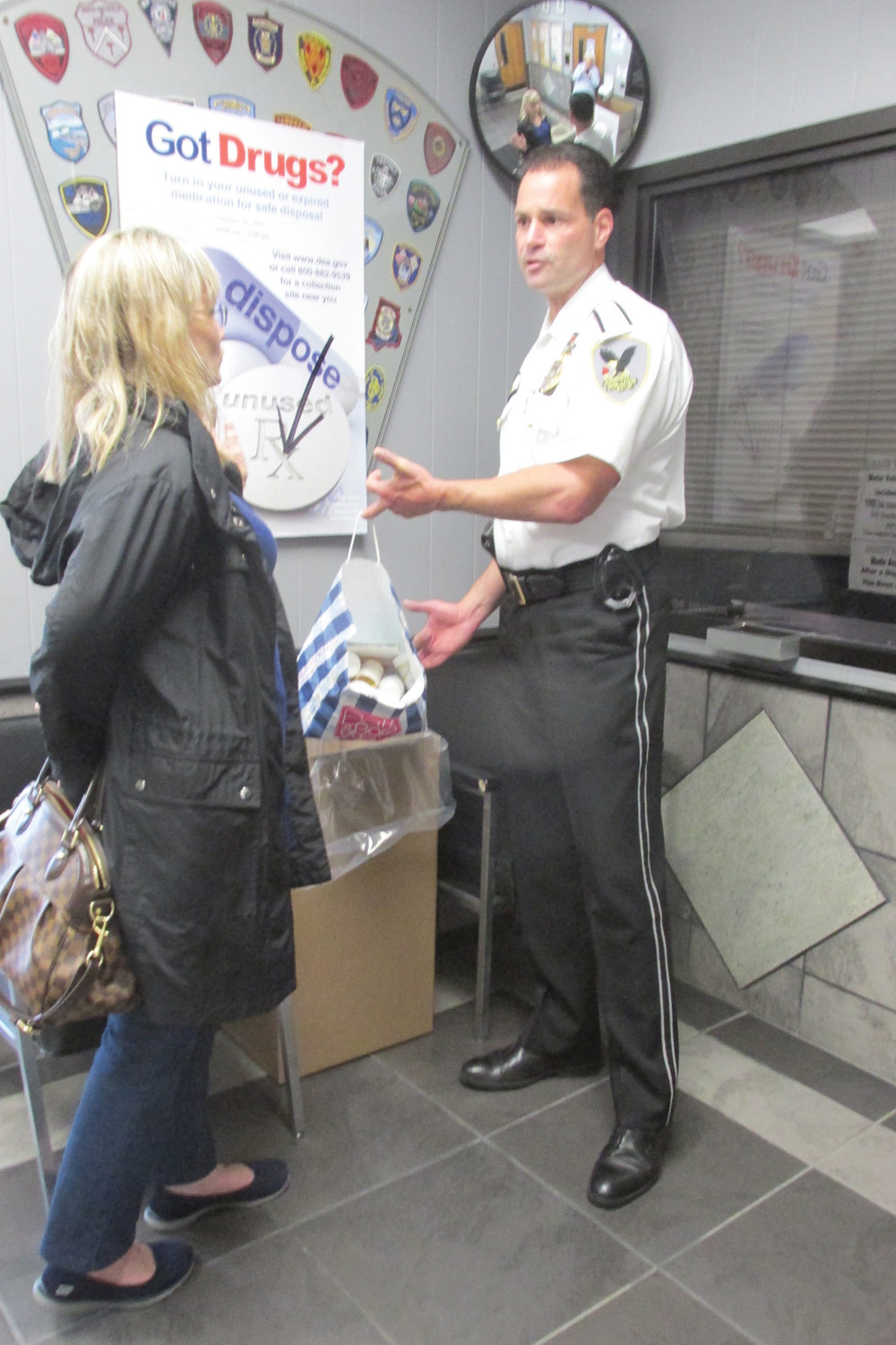 HEAVY HAUL: Deputy Chief Joseph P. Razza explains the importance of National Drug Take Back Day to this woman who brought a big bag of unused drugs to JPD headquarters Saturday. (Sun Rise photos by Pete Fontaine)